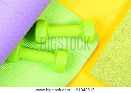 Dumbbells On Green And Purple Yoga Mat And Towel