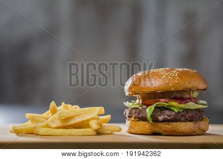 A fresh tasty burger with potatoes on the table, in a cafe