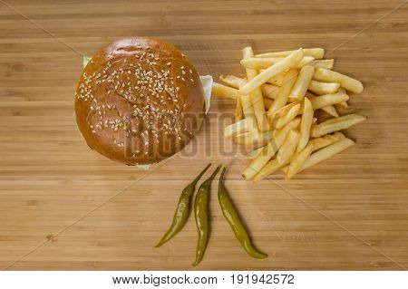 Fresh appetizing burger with pepper and potatoes, top view