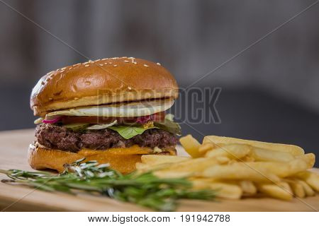 Big fresh appetizing burger with pepper and potatoes, top view