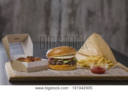 Delicious hamburger lunch with potatoes and chicken, on the table