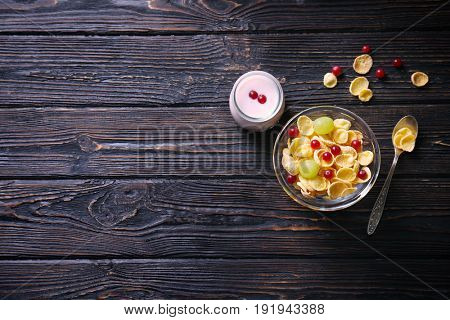 Delicious corn flakes and yogurt on wooden table
