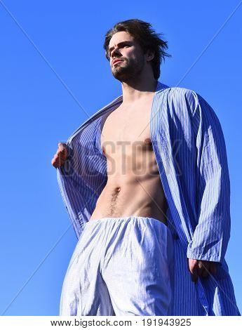 Bearded man short beard. Caucasian macho with moustache and ruffled hair in blue striped pajamas and stylish hat showing strong torso with six packs on blue sunny sky background
