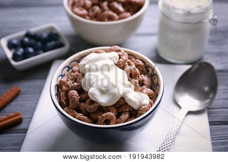 Chocolate corn rings with yogurt on wooden table