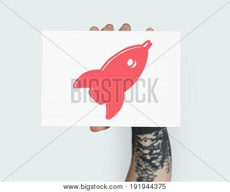 Hand holding placard with rocket start up icon