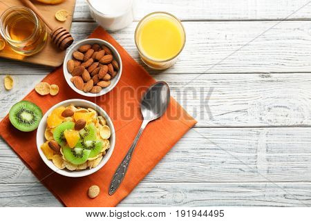 Corn flakes with fruits and almonds on table