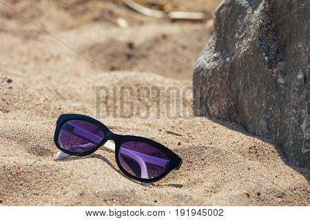 Glasses with a dark rim on the sand