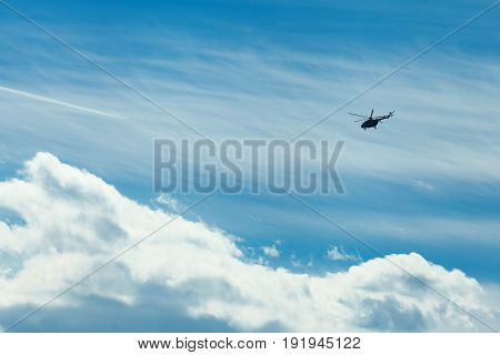 One helicopter on a background of a cloudy blue sky