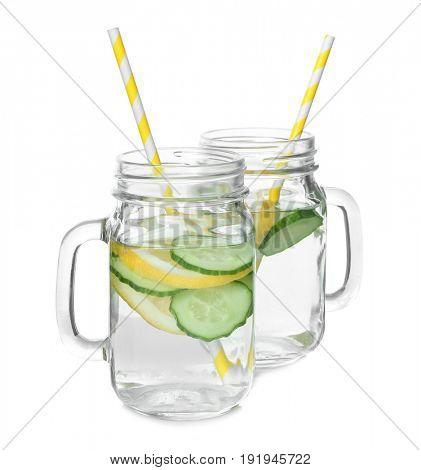 Tasty refreshing lemonade with cucumber in mason jars on white background