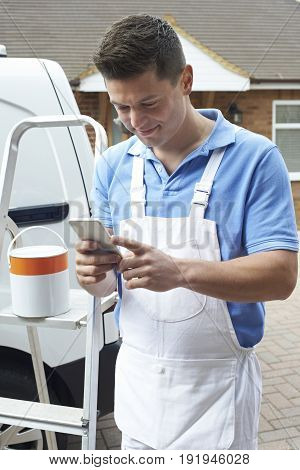 Decorator Using Mobile Phone Standing Outside Domestic Home