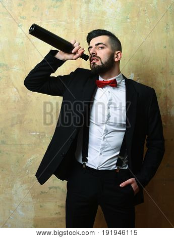 Man with beard in suit and red bow drinks wine with arrogant face expression on background of beige color wall. Concept of leisure and pub party