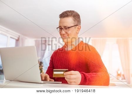 Mature man using credit card and laptop to shop online during Christmas