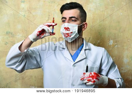 Doctor With Bloody Hands In Surgial Mask Looks At Syringe