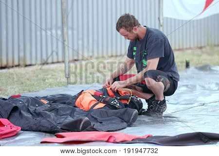 Sky Diver Packing And Checking Chute Before Next Jump.