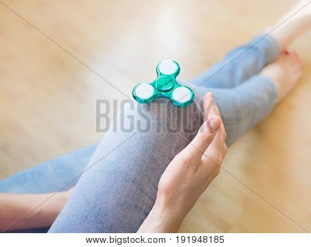 Girl playing with a glossy light colourful hand fidget spinner toy.