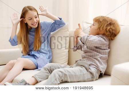Family relations. Cute motional energetic children sitting on a couch and goofing around while spending time together at home