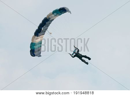 Male Sky Diver With Brightly Coloured Open Parachute Gliding In Sideways For Landing