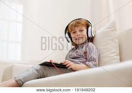 Little artist. Savvy smart adorable child using his gadget for listening to some songs while sitting on a couch and wearing headphones