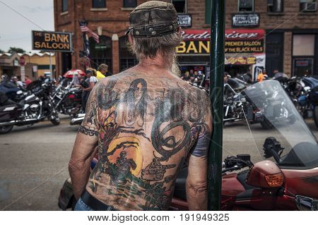 Sturgis South Dakota - August 8 2014: Man with a tattoed back looking at the bikes in the city of Sturgis South Dakota USA during the annual Sturgis Motorcycle Rally
