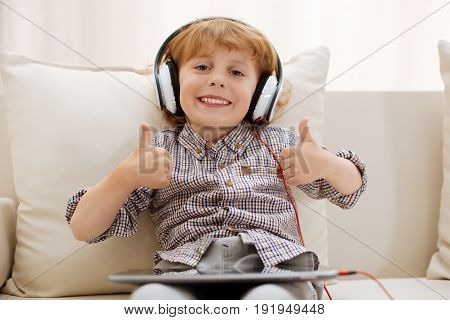 Enthusiastic listener. Cheerful charismatic good looking boy spending his free time at home and enjoying video games while using his tablet and wearing headphones