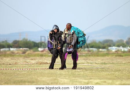 European White Male Walking And Talking With Black African Skydiver After Successful Landings