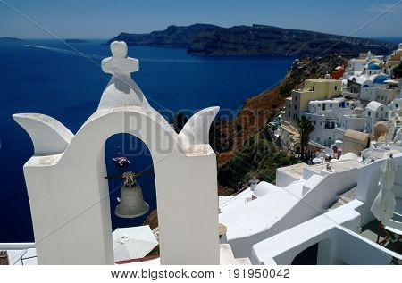 Beautiful view of Oia with a bell tower in the foreground