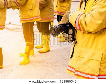 fireman hold fire hose nozzle. Firefighters training.