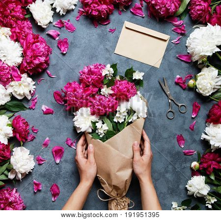 Female florist holding beautiful bouquet at flower shop. Florist at work: pretty woman making summer bouquet of peonies on a working gray table. Kraft paper, scissors, envelope for congratulations.