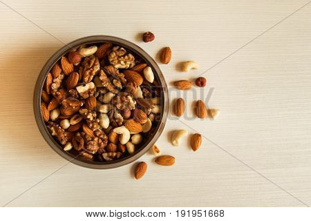 Mixed Nuts In A Metal Brown Bowl On A White Wooden Background.