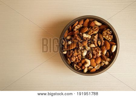 Mixed Nuts In A Metal Bowl On A White Wooden Background.