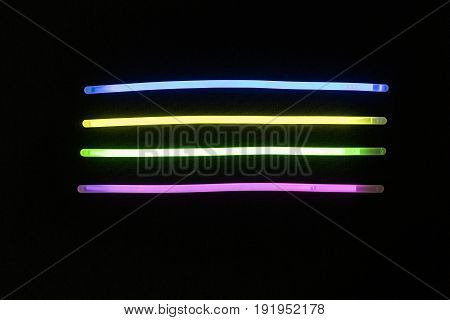 Glow sticks neon light fluorescent on back background. variation of different colored chem lights