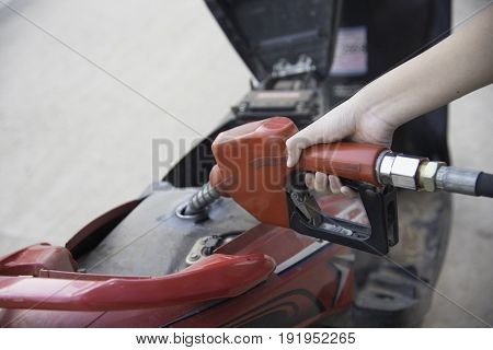 female hand refilling the motorcycle with fuel on a filling station