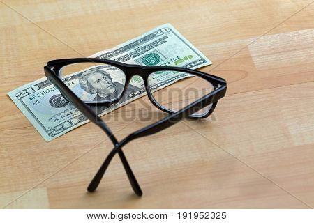 Spectacles with black frame, eye glasses on 20 USD dollar banknote money bill focusing on face, on wooden background