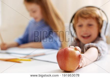 Sweet snack. Adorable diligent active boy feeling hungry after completing his home assignment while his sister still working on it