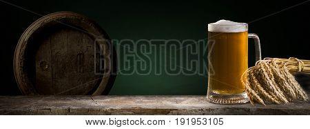 Beer in mug on wooden table near brick wall.