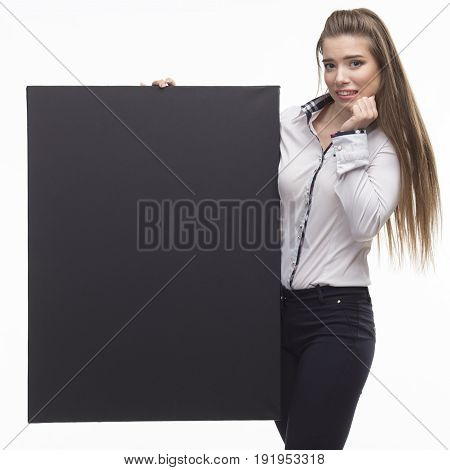 Young scared woman portrait of a confident businesswoman showing presentation, pointing placard black background. Ideal for banners, registration forms, presentation, landings, presenting concept.