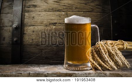 Beer in mug on wooden table near brick wall.
