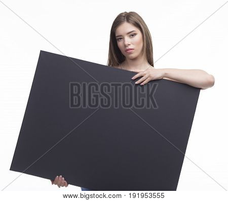 Young sexy woman portrait of a confident businesswoman showing presentation, pointing paper placard black background. Ideal for banners, registration forms, presentation, landings, presenting concept.