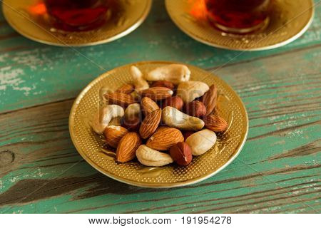Mixed Nuts On A Yellow Metal Saucer And Two Glass Cups Of Turkish Tea On A Turquoise Wooden Backgrou