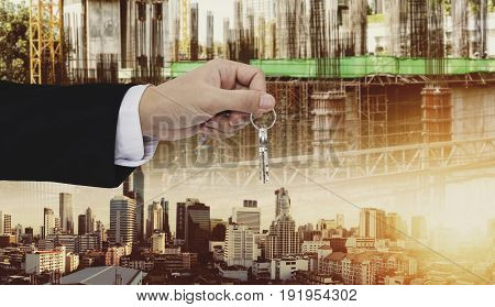 Hand holding keys, with site construction and city in sunset background