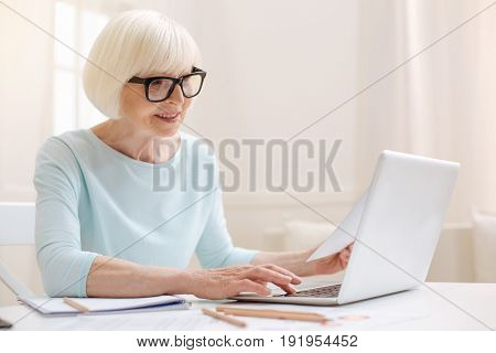 Aged expert. Cheerful productive ambitious woman working on her review of the article she reading while typing it on her computer