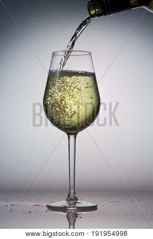 Pouring white wine from bottle to glass