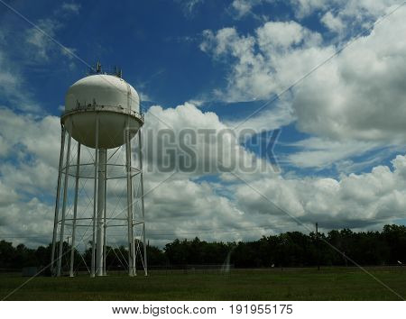 Huge water tank with backdrop of white fluffy clouds A huge white water tank standing in a field with white fluffy clouds in the skies