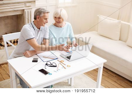 Best advisor. Motivated bright elderly gentleman giving his wife an advice while they discussing a business project she working on