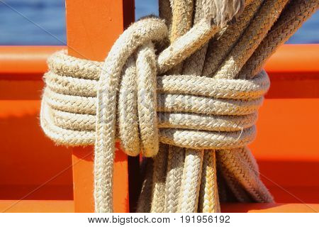 Big ropes tied in a tight knot Sturdy white ropes tied in a secure tight knot against a wood post