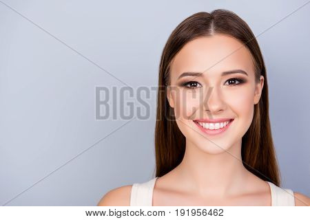 Close Up Cropped Photo Of Young Cute Charming Lady On The Pure Light Blue Background, Has Toothy Smi