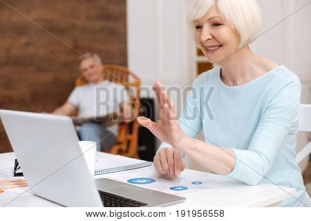 Hello, my dear. Friendly energetic elegant lady using internet for getting in touch with her buddy while sitting in a living room with her husband
