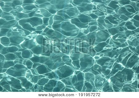 Clear water with reflections from the sun A backdrop of clear water in a swimming pool reflected by the sun, creating lines and ripples
