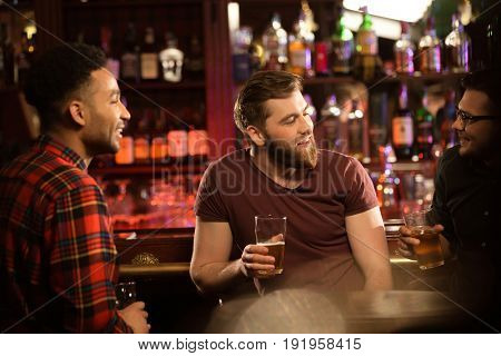 Smiling young men drinking beer, talking and smiling while resting at the pub