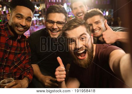 Cheerful old friends having fun by taking selfie and drinking draft beer in pub